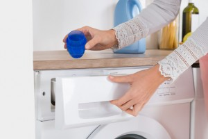 Female Hands Pouring Detergent In The Washing Machine